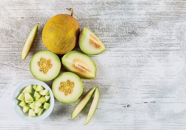 Du melon en tranches avec du melon dans un bol sur fond de pierre blanche, vue du dessus. copier l'espace pour le texte