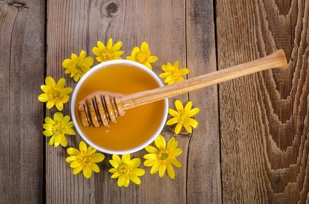 Du miel dans le bol en verre et des fleurs jaunes autour