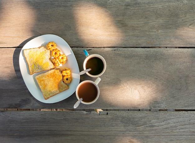 Du pain au beurre, des biscuits farcis à l'ananas et du café chaud sont placés sur une table en bois.