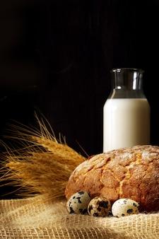 Du pain et du lait sur une table sur un fond sombre, éclairé par les rayons du soleil.