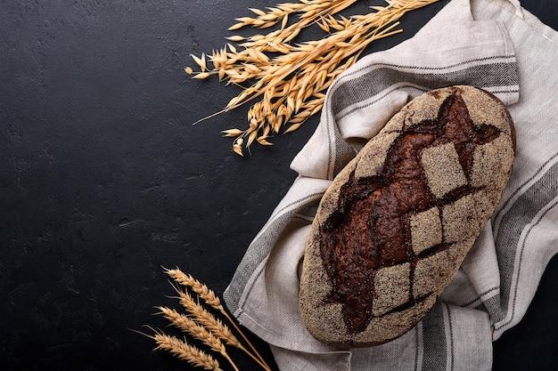 Du pain maison fraîchement cuit sur du seigle au levain artisanal sur fond de pierre noire ou de béton. vue de dessus. fond de cuisson des aliments. espace de copie.