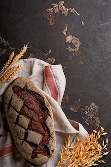 Du pain maison fraîchement cuit sur du seigle au levain artisanal sur fond de pierre de taille ou de béton. vue de dessus. fond de cuisson des aliments. espace de copie.