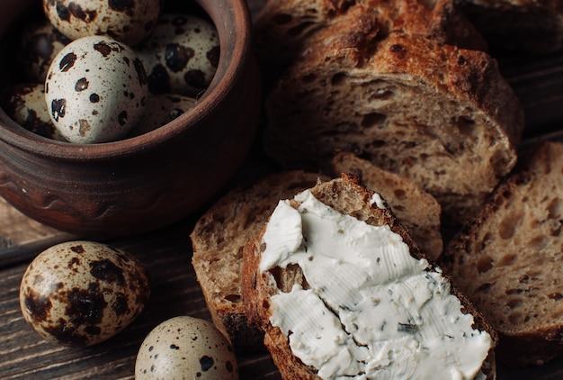 Du pain noir au sarrasin est tartiné de fromage cottage avec des herbes dans une coupe sur une table en bois près des œufs de caille dans une assiette en argile de style rustique.