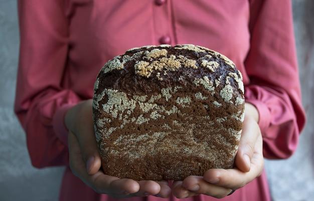 Du pain noir dans les mains. fermer.