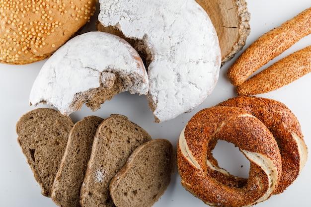 Du pain en tranches avec du bagel turc sur une surface blanche, vue du dessus.