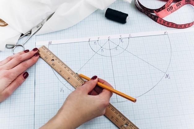 Du papier blanc, du ruban à mesurer, du tissu, des aiguilles, du fil, des ciseaux et du papier se trouvent sur la table