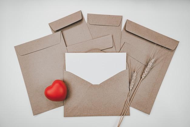 Du papier blanc vierge est placé sur l'enveloppe de papier brun ouverte avec coeur rouge et fleur sèche d'orge