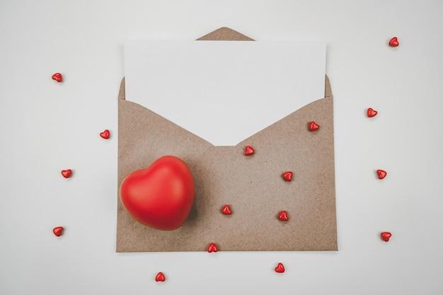 Du papier blanc vierge est placé sur l'enveloppe de papier brun ouverte avec un cœur rouge