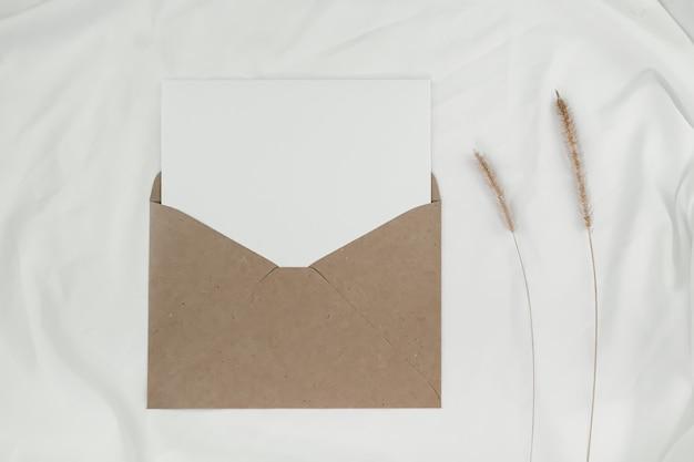 Du papier blanc vierge est placé sur l'enveloppe de papier brun ouverte avec une fleur sèche de sétaire hérissée sur un tissu blanc. enveloppe de papier craft sur fond blanc.