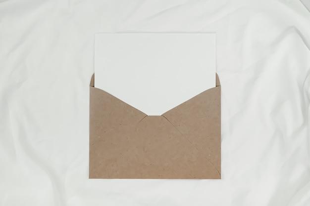 Du papier blanc vierge est placé sur l'enveloppe de papier brun ouverte sur un tissu blanc. vue de dessus de l'enveloppe de papier craft sur fond blanc.