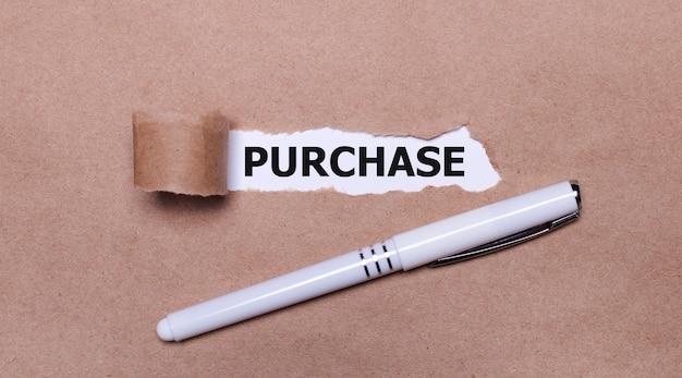 Sur du papier kraft, un stylo blanc et une bande de papier blanc avec le texte achat.