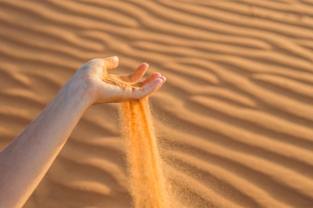 Du sable glissant entre les doigts de la main d'une femme dans le désert.