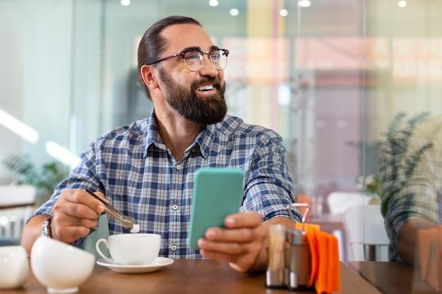 Du sucre. homme souriant barbu mettant du sucre dans son café assis à la cafétéria tenant son téléphone