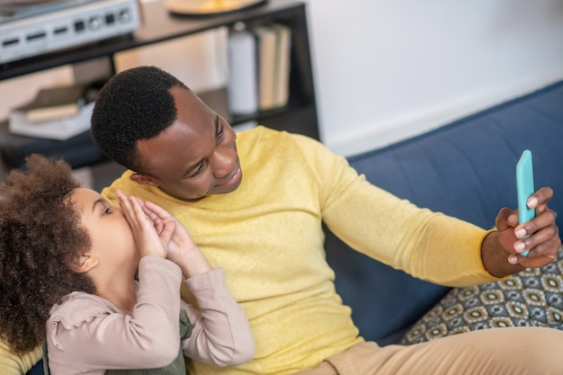 Du temps avec papa. papa heureux noir en pull jaune regardant l'écran du smartphone dans la main tendue et la petite fille sur le canapé