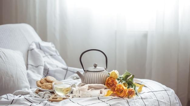 Du thé, des biscuits et un bouquet de tulipes fraîches au lit. petit-déjeuner et concept de matin de printemps.