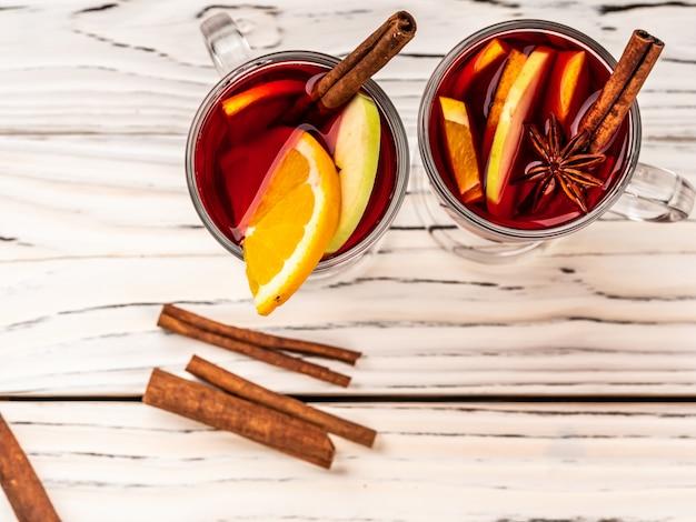 Du vin chaud avec des épices et des bâtons de cannelle se dresse sur une table en bois blanc. copiez l'espace.