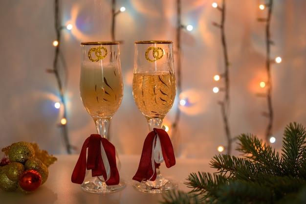 Du vin mousseux est versé dans des verres du nouvel an sur fond de guirlande lumineuse.