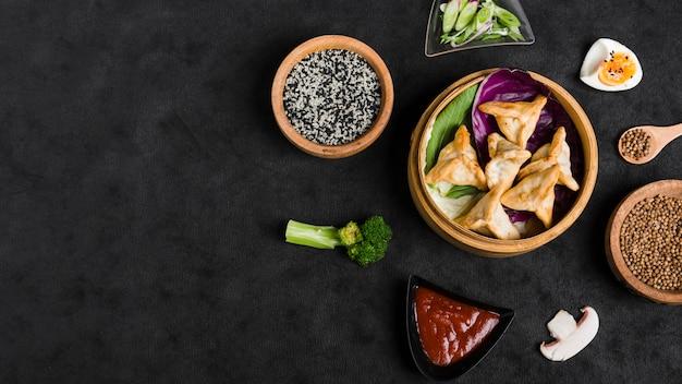 Dumpling à la vapeur entouré d'ingrédients sur fond texturé noir