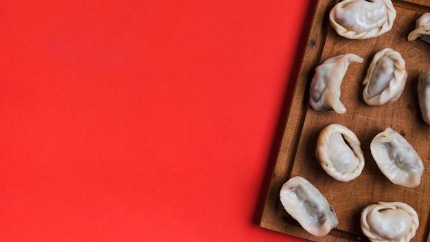 Dumplings sur un bureau en bois sur fond rouge