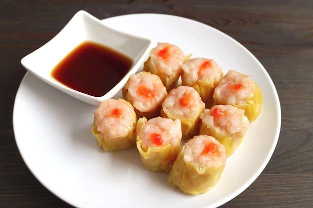 Dumplings chinois cuits à la vapeur remplis de crevettes et de porc savoureuses appelées shumai sur une assiette blanche
