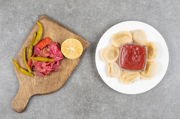 Dumplings farcis à la viande et divers légumes marinés