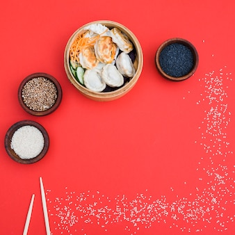 Dumplings in steamer avec graines de coriandre; bol de graines de sésame noir et blanc sur fond rouge
