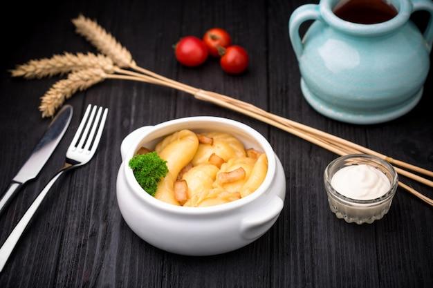 Dumplings avec pommes de terre et cracknel sur fond en bois noir