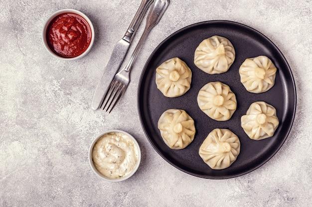Dumplings traditionnels cuits à la vapeur khinkali avec sauce tomate et tartare