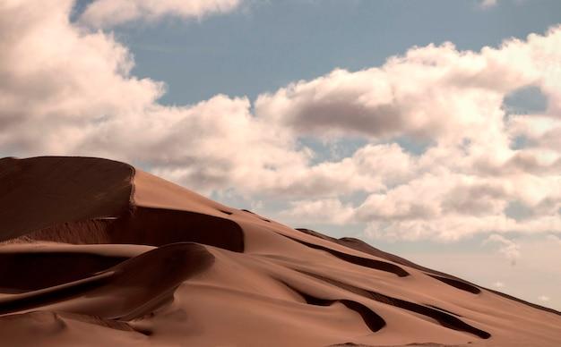 Dune de sable doré 7 et nuages blancs sur une journée ensoleillée dans le désert du namib.