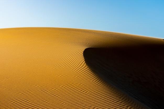 Dunes de sable doré au coucher du soleil avec un côté d'ombre à corralejo fuerteventura