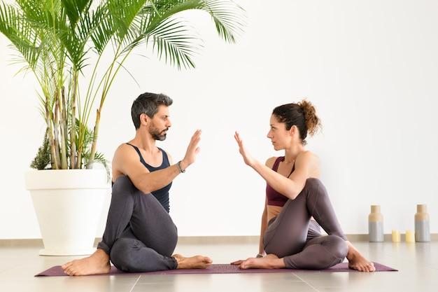 Duo homme et femme faisant des exercices d'étirement de yoga