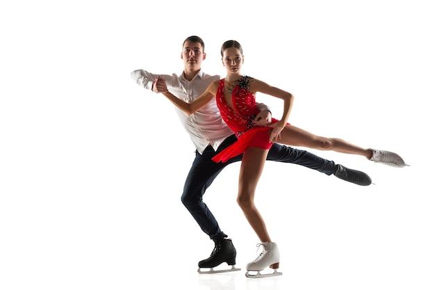 Duo de patinage artistique isolé sur fond de studio blanc avec copyspace