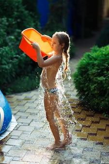 Le durcissement du corps. une charmante fillette de sept ans s'asperge d'eau froide d'un bassin rouge par une journée ensoleillée d'été.