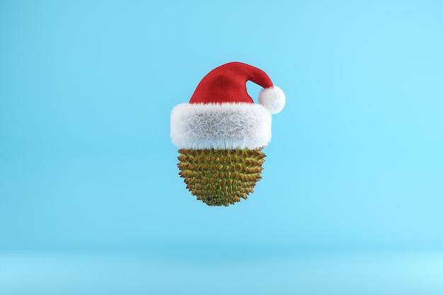 Durian avec bonnet de noel flottant sur bleu
