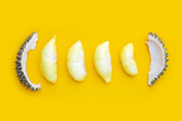 Durian frais coupé mûr sur fond jaune.