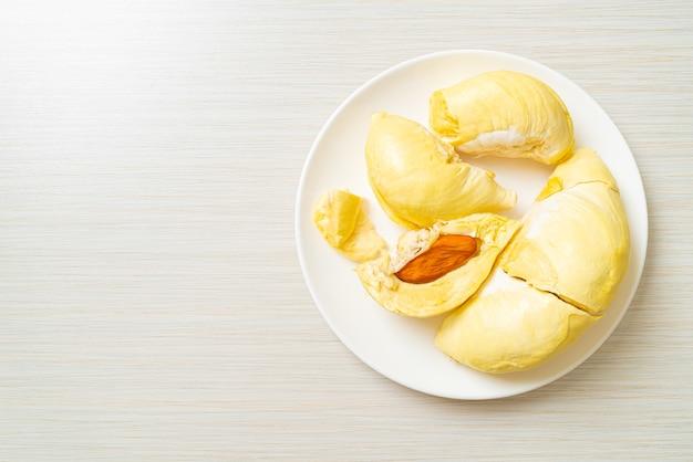 Durian mûri et frais, peau de durian sur plaque blanche