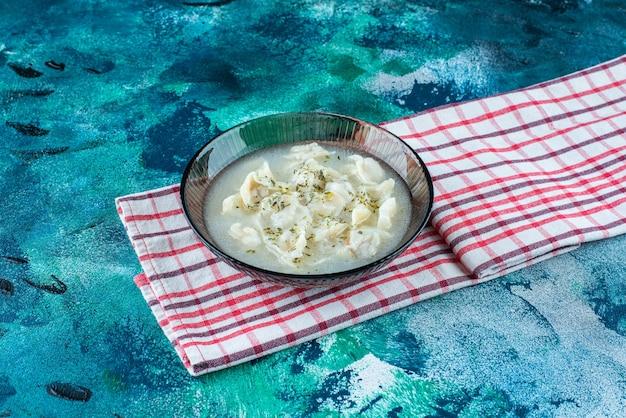 Dushbara dans une assiette sur une serviette, sur le fond bleu.