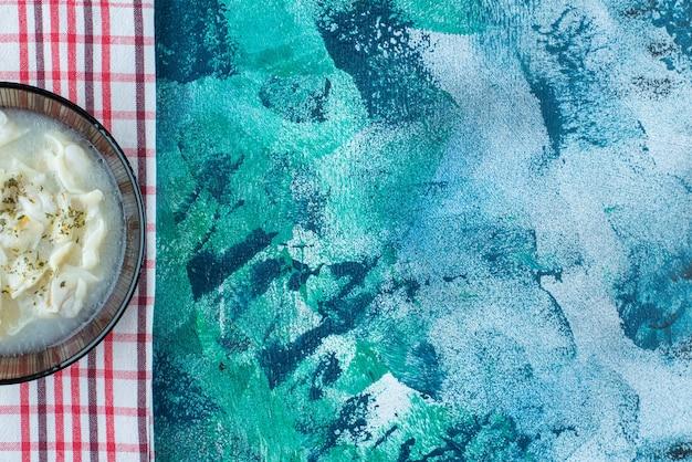Dushbara dans une assiette sur une serviette, sur la table bleue.