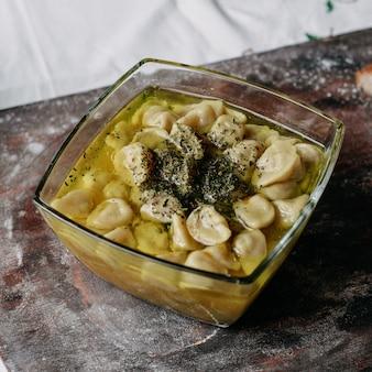 Dushpere viande célèbre viande hachée orientale à l'intérieur du repas avec bouillon sur le bureau brun