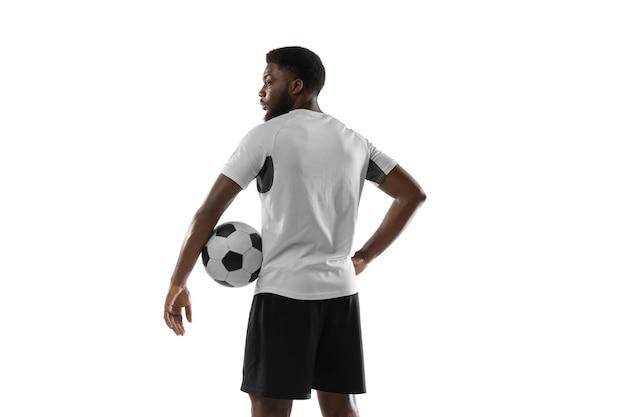 Dynamique. jeune homme africain, formation de joueur de football masculin isolé.
