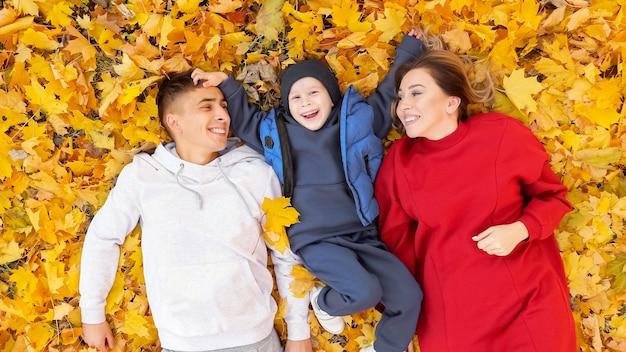 E al jeune famille de mère père et petit garçon passent du temps allongé sur le sol avec un tapis de feuilles jaunes sèches dans le parc d'automne vue supérieure