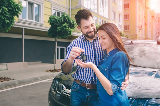 E avez fait le bon choix. beaux jeunes hommes debout près de la voiture chez le concessionnaire étreignant sa petite amie et tenant une clé