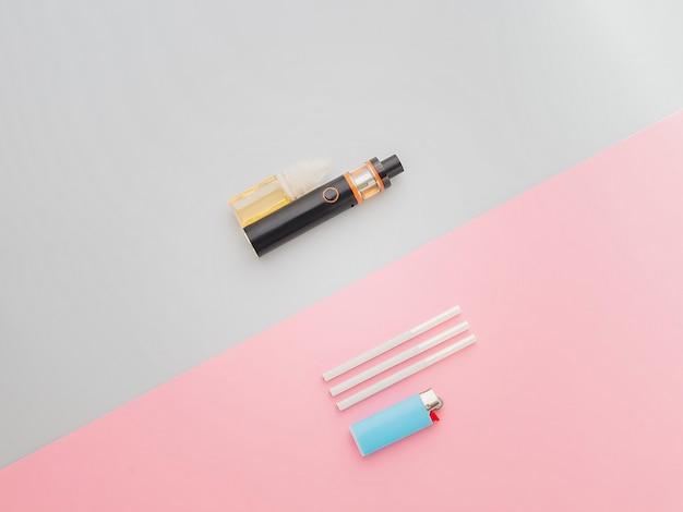 E-cigarette pour vapoter avec une cigarette normale sur le sol bleu et rose