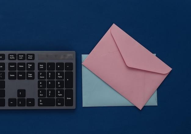E-mail. clavier pc et enveloppes sur un bleu classique.