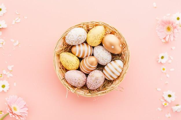 Easter flat lay of eggs avec des fleurs rose