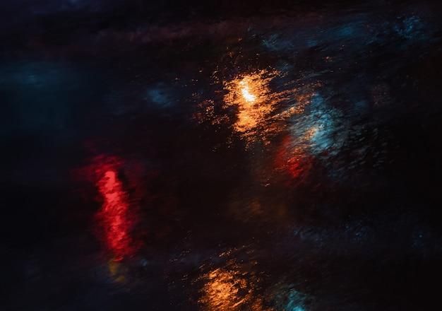 L'eau abstraite tâtonne l'arrière-plan. gouttes d'eau et éclaboussures sur le verre sur un fond sombre illuminé de lumières colorées. ruisseau et gouttes coulant dans le verre