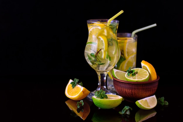 Eau au citron vert, feuilles de menthe citronnée sur fond noir