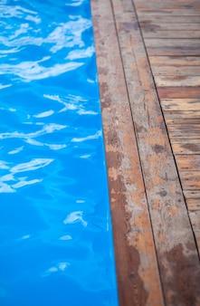 Eau bleue et claire dans une piscine en plein air. les bords de la piscine sont en bois. fond d'eau, ondulation et flux avec des vagues. mer, surface de l'océan. vue de dessus avec place pour le texte.