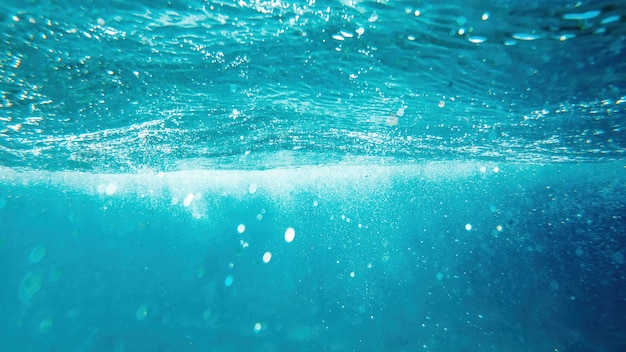 Eau bleue et transparente de la mer méditerranée. lumière du soleil, plusieurs bulles