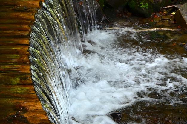 L'eau en bois faite à la main s'écoule des petites poutres traitées.